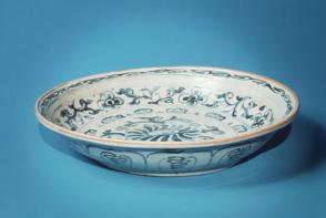 Blue and white dish: blossom and floral scroll decor.